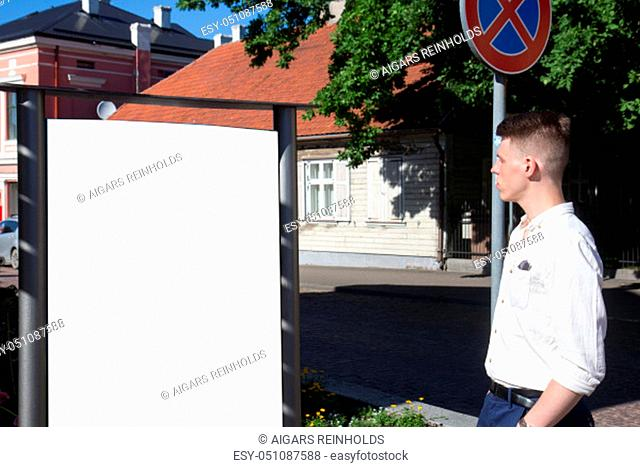Man looking at empty billboard standing in outdoors on street