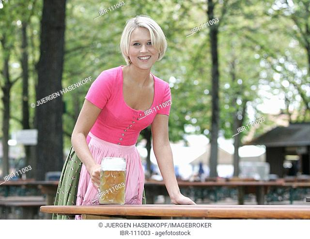 Portrait of a young blonde woman wearing a dirndl in a beergarden