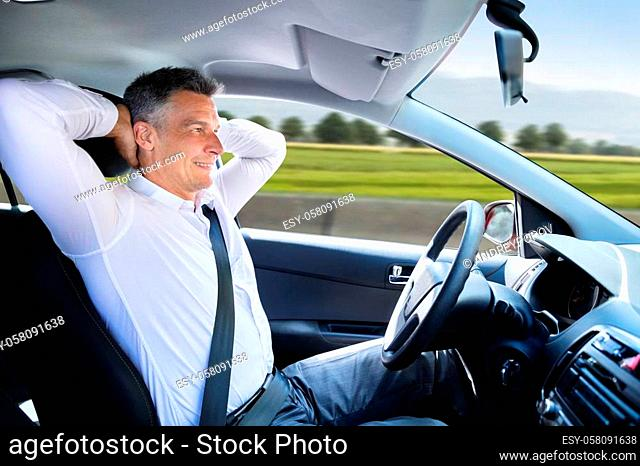Side View Of A Relaxed Mature Man Sitting In Autonomous Self Driving Car
