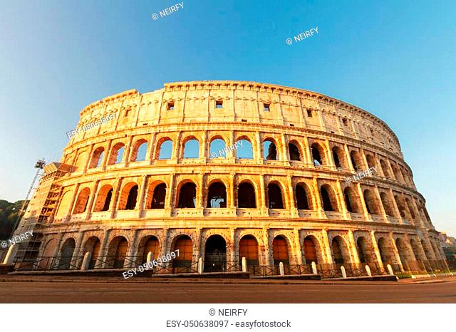 view of famous ruins of Colosseum at sunrise in Rome, Italy