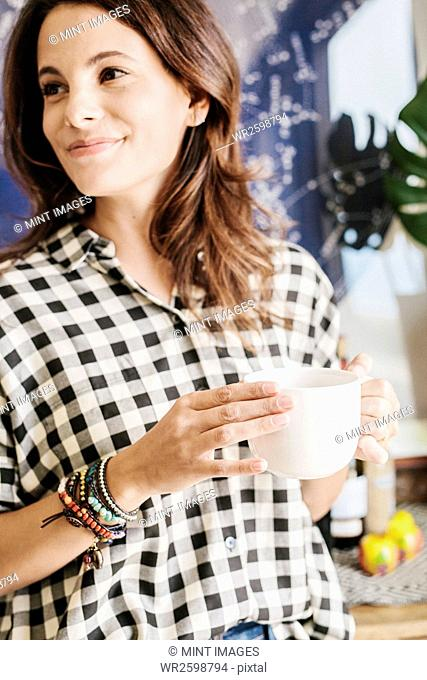 Woman with long brown hair, wearing a chequered shirt, holding a mug