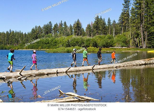 Children on Log in Manzanita Lake, Lassen Volcanic National Park, California, USA