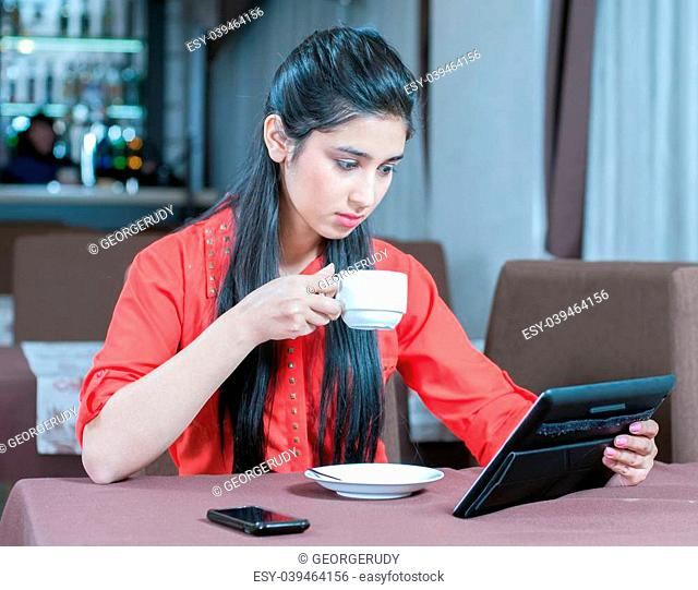 Young indian businesswoman on a coffee break. Using tablet computer