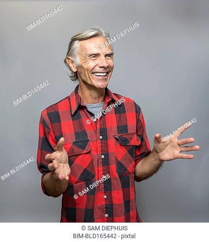 Smiling older Caucasian man gesturing