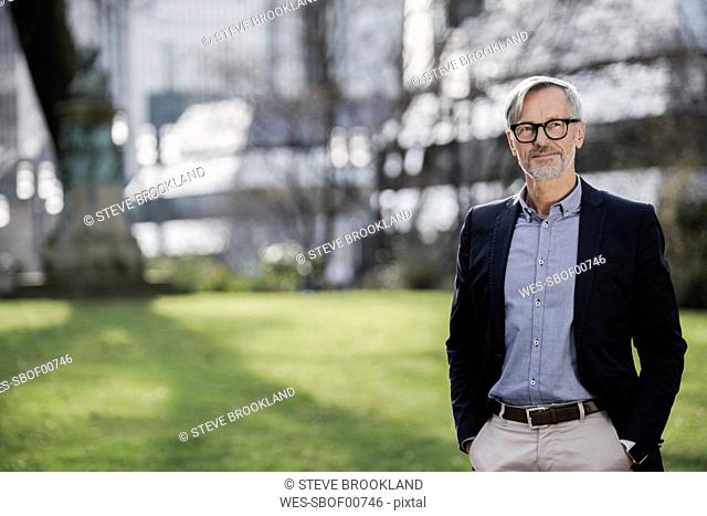 Grey-haired businessman in city park