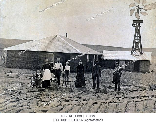 A farm family standing in front of sod house and windmill. Coburg, Nebraska 1885