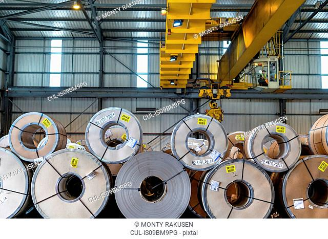 Crane over rows of sheet steel in storage at port
