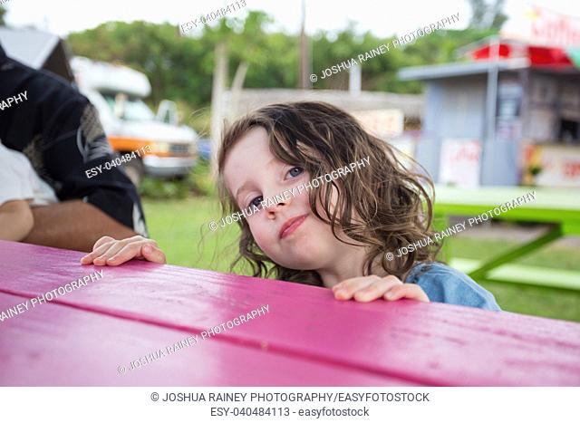 Three year old girl lifestyle portrait at a picnic table next to a food truck in Oahu Hawaii