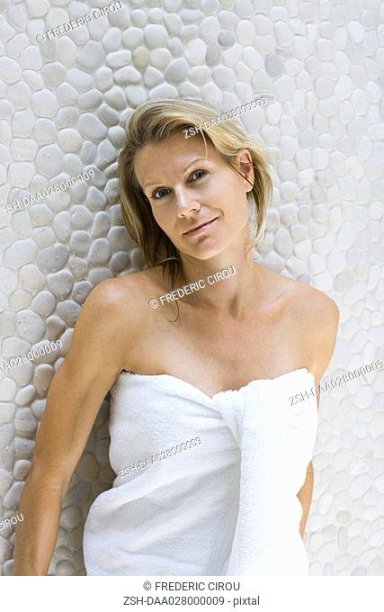 Woman wrapped in towel, leaning against wall, smiling at camera