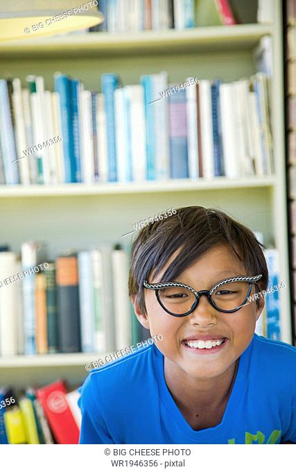 Boy wearing vintage glasses smiles in front of a bookcase