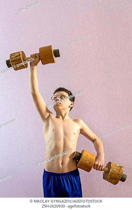 Young athlete exercise with wooden dumbbells