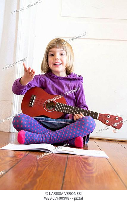 Portrait of little girl sitting on wooden floor playing ukulele