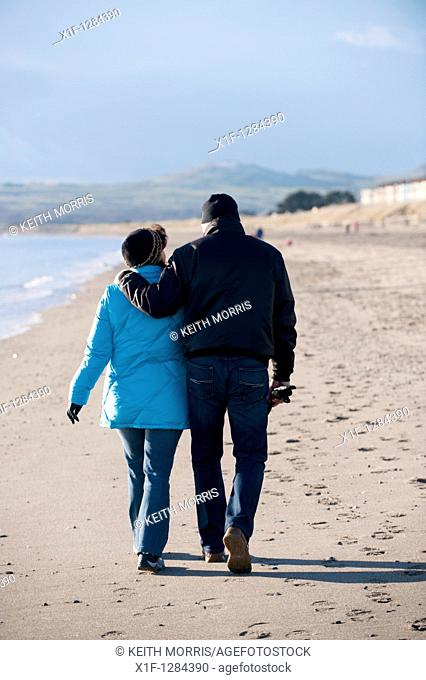 A couple walking alomng Pwllheli beach, winter afternoon, snowdonia national park, north wales UK