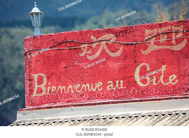 Red french language sign on bed and breakfast roof terrace wall, Reunion Island