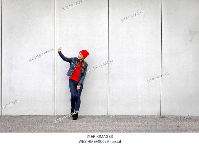Woman wearing red pullover and wolly hat and taking a selfie in front of a wall