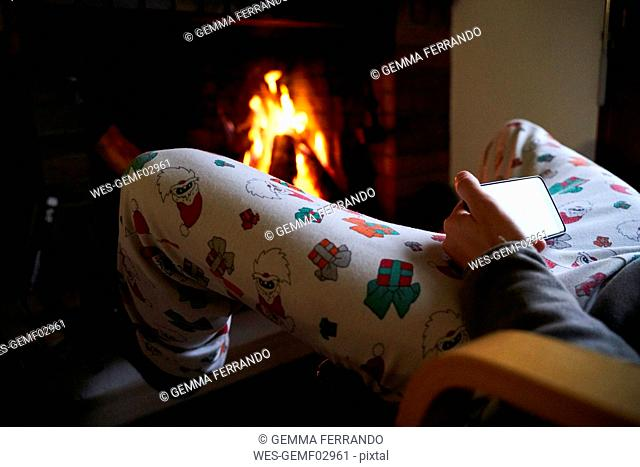 Man sitting in front of fireplace wearing Santa Claus Christmas pants using mobile phone