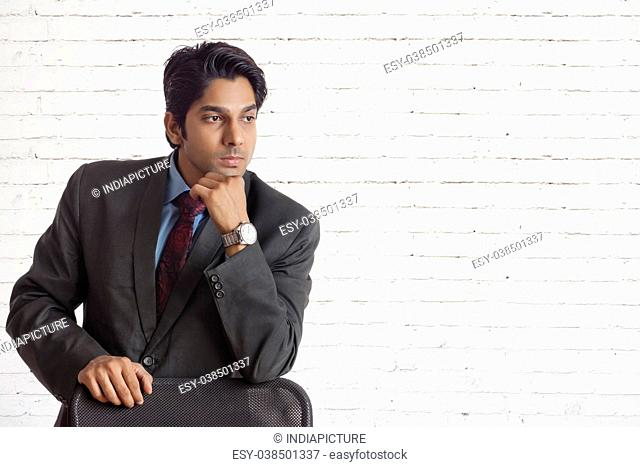 Confident businessman leaning on chair hand over his mouth