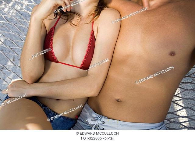 Midsection of couple sitting together in hammock