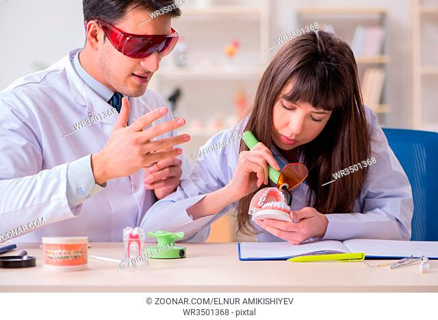 Doctor explaining to assistant how to use ultraviolet gun