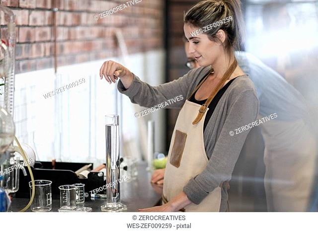 Woman working with liquid in distillery