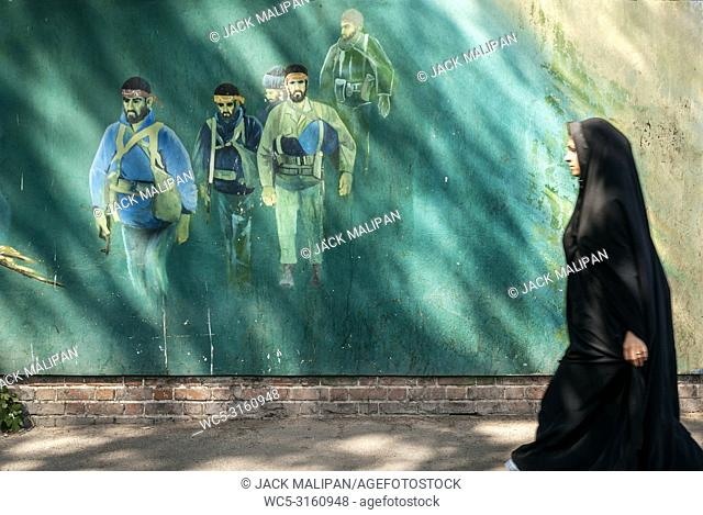 veiled muslim woman walking by revolutionary fighters mural in downtown tehran city street iran outside old US american embassy