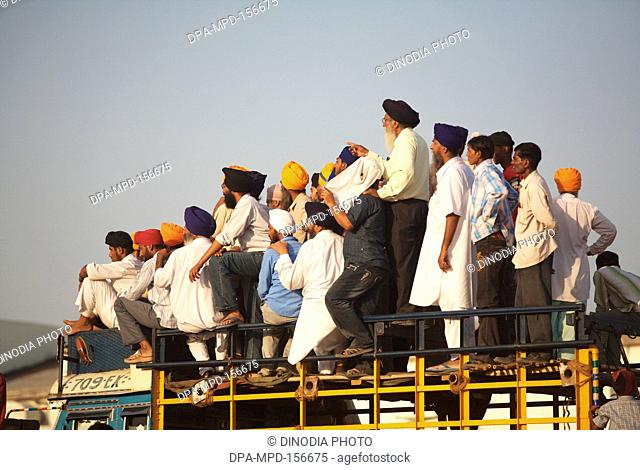 Sikh devotees standing on top of truck watching stunts of Nihangs or Sikh warrior ; during cultural events for 300th year's celebrations of Consecration of...