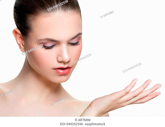 Cute young woman showing empty copy space on the open hand isolated on white background. Female face closeup. Skincare and wellness concept