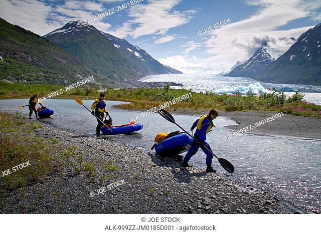 Three women pull their packrafts along the shore of Spencer Glacier Lake, Kenai Mountains, Southcentral Alaska, Summer