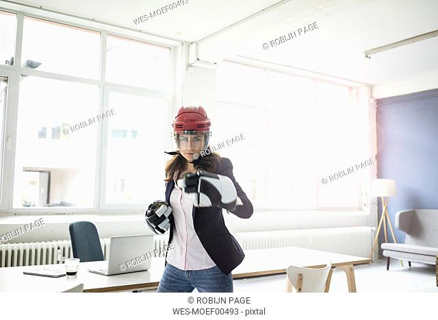 Portrait of businesswoman wearing ice hockey equipment in the office