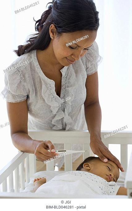 African American mother checking baby's temperature