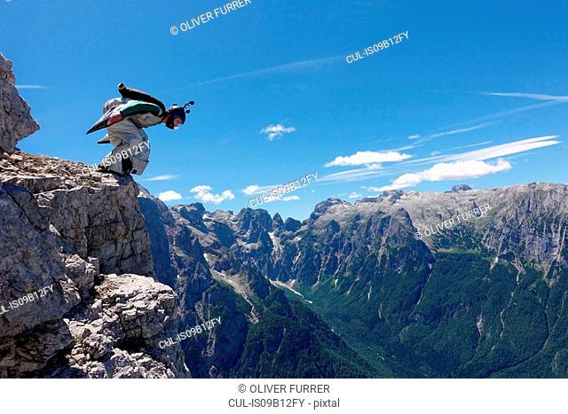 Wingsuit BASE jumper getting ready to jump from cliff, Italian Alps, Alleghe, Belluno, Italy