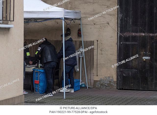 21 February 2019, Hessen, Biebesheim: Criminal police officers (l) secure previously seized evidence in the backyard of a house near the railway station