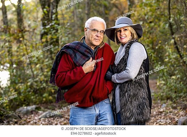 A happy 65 year old man and a 59 year old blond woman walking together in a forest setting, smiling at the camera