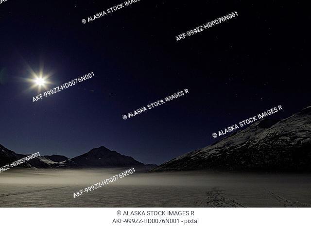 A full moon illuminates Bold Peak and ground fog on frozen Eklutna Lake in Chugach State Park in Southcentral Alaska, Winter