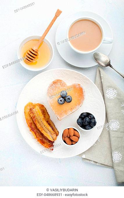 A stack of delicious pancakes with honey, coffee and blueberries on a light blue background. Great Breakfast for Valentine's day. Top view