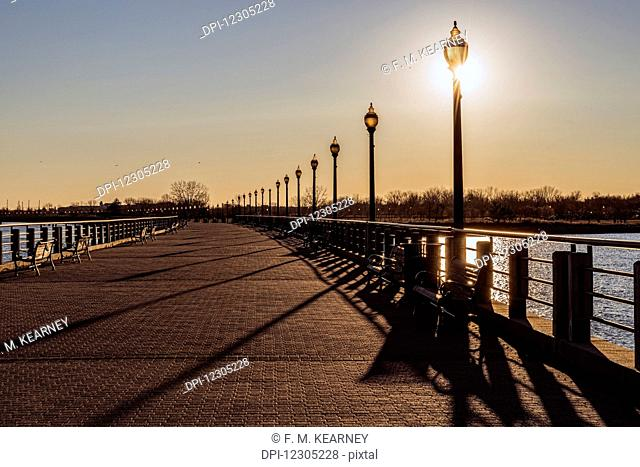 Sun setting behind lampposts, Liberty State Park; Jersey City, New Jersey, United States of America