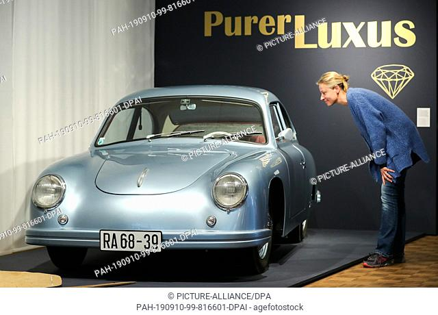 """10 September 2019, Saxony, Leipzig: A woman looks at a GDR Porsche built by two hobbyists themselves in the exhibition """"""""Pure Luxury"""""""" in the Contemporary..."""