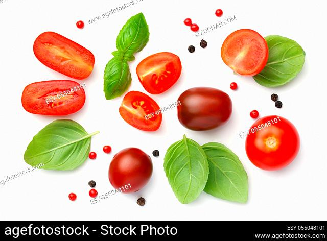 Composition with red, brown cherry tomatoes, basil and peppercorns isolated on white background. Top view