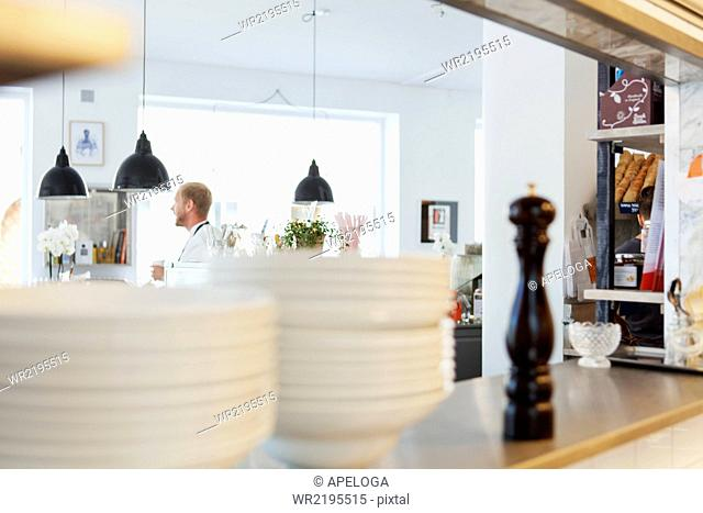 Stack of plates on restaurant counter with chef in background