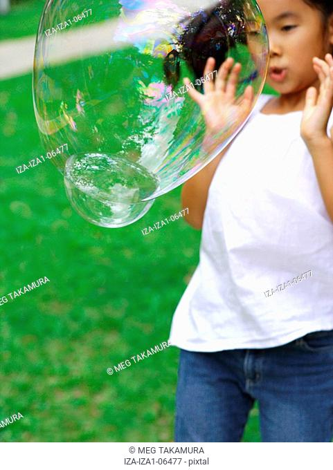 Girl standing in a garden and watching a soap bubble