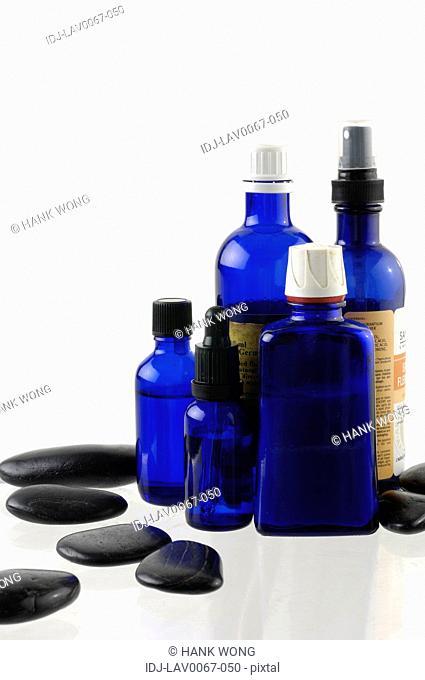 Massage oil bottles near pebbles