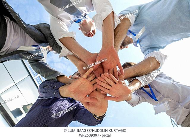 Group of business people stacking hands in a circle