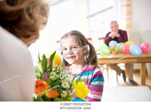 Granddaughter hand over bunch of flowers to her grandmother while grandfather in background