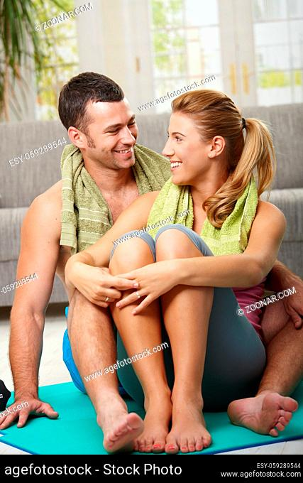 Happy couple resting after training, sitting on fitness mat in living room, looking at each other smiling