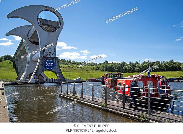Canal boat with tourists mooring at Falkirk Wheel, rotating boat lift, Stirlingshire, Scotland, UK