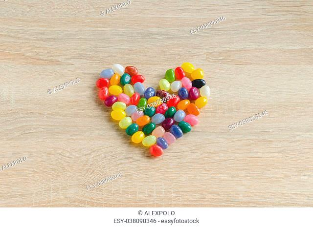 Heart symbol from jelly beans on wooden background