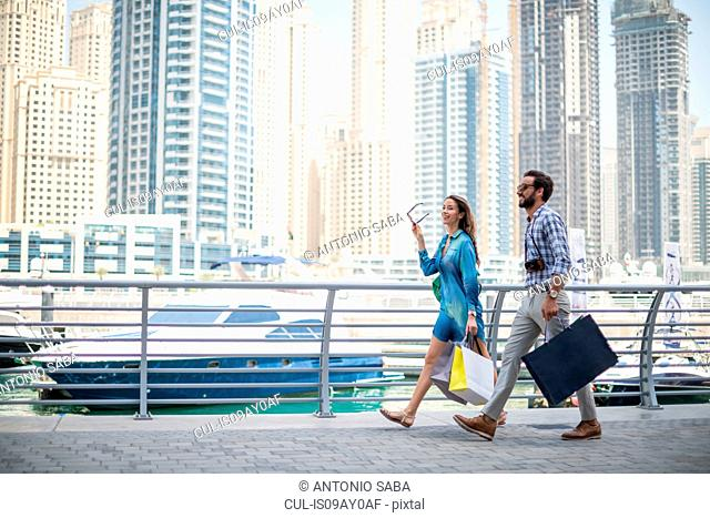Couple strolling on waterfront carrying shopping bags, Dubai, United Arab Emirates