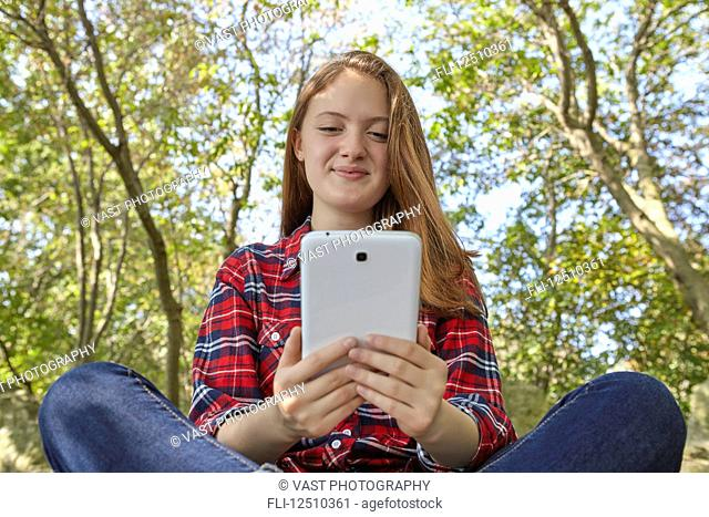 A teenage girl wearing jeans and a plaid shirt sits on a boulder using her smart phone, Woodbine Beach; Toronto, Ontario, Canada