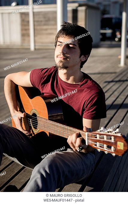 Young man sitting on a bench playing guitar