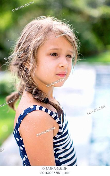 Girl gazing by outdoor swimming pool
